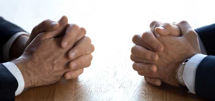 Manos cruzadas frente a frente sobre un escritorio