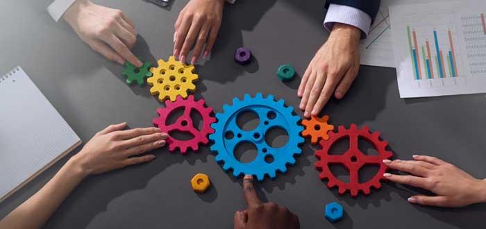 Manos y engranajes de colores sobre una mesa