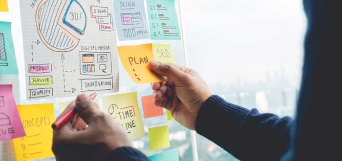 Manos de un hombre con un tablero de notas que incluyen las cualidades de un emprendedor