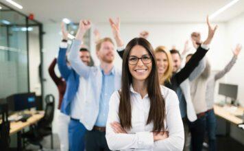Mujer con los brazos cruzados y su equipo de trabajo detrás con los brazos levantados