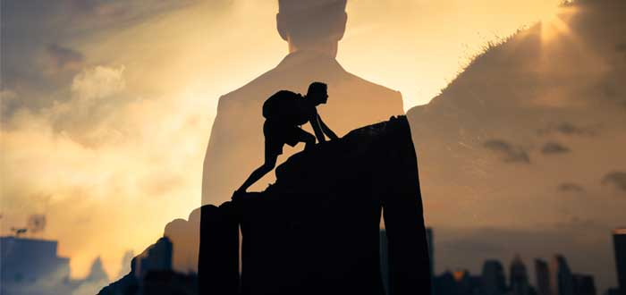 Silueta de un hombre de espaldas superpuesta a una silueta de hombre subiendo una montaña