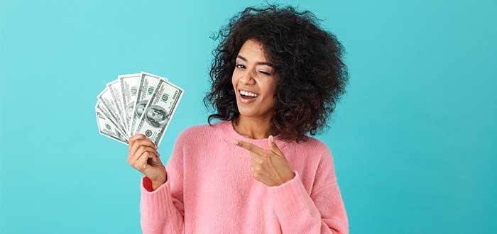 mujer dinero en la mano señalando con la otra mano