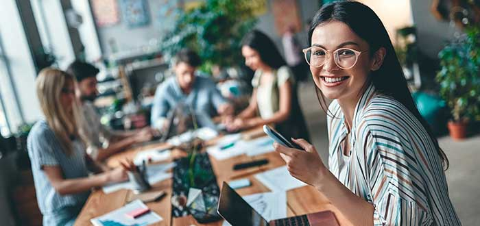 Mujer sonríe celular en la mano compañeros en el fondo frases para iniciar la semana