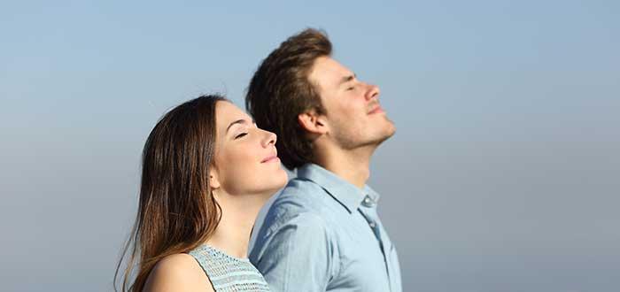 Hombre y mujer inspiran cerrando ojos frases para iniciar la semana
