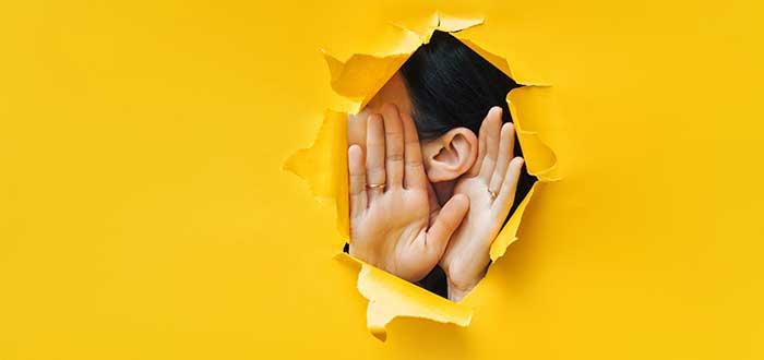 oreja y manos salen de una pared