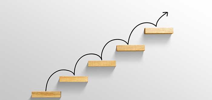 escalera en pared blanca con flechas ascendentes liderazgo empresarial
