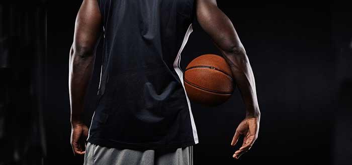 hombre negro de espaldas con bola de basquetbol