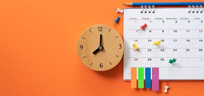 reloj y planeador con chinches y papeles para anotar liderazgo empresarial