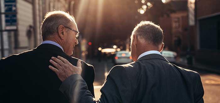 dos hombres caminan por la calle y hablan liderazgo empresarial