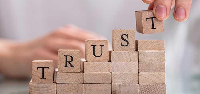 manos armando bloques con letrero trust