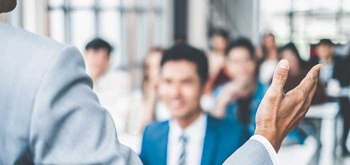 persona de espaldas habla a un grupo de personas liderazgo empresarial
