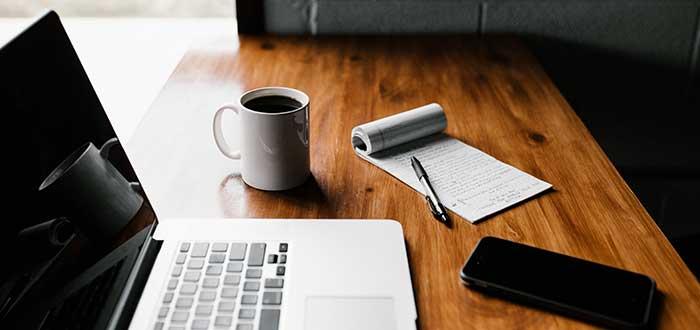 libreta, bolígrafo y laptop encima de mesa
