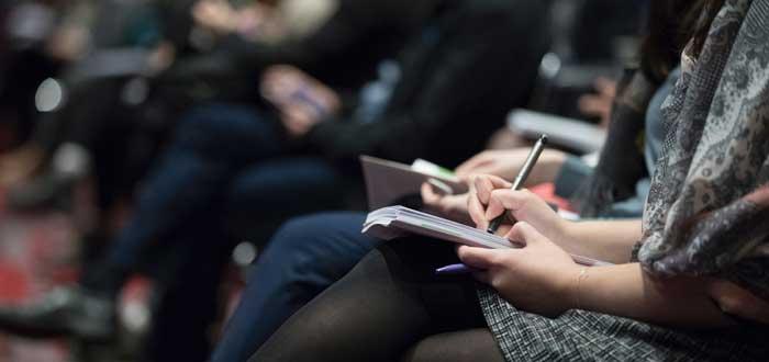 personas apuntando objetivos asignados en reuniones efectivas