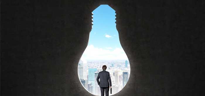 Silueta de bombilla y ejecutivo mirando a la ciudad
