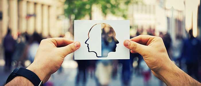 persona sostiene una imagen de dos caras mirando a lados diferentes
