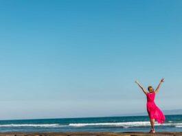 Mujer vestida de rojo frente al mar
