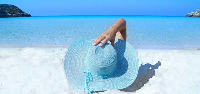 Mujer con sombrero en la playa ideando estrategia del oceáno azul
