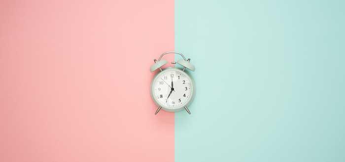 Relojo entre un cuadrado rosa y uno verde