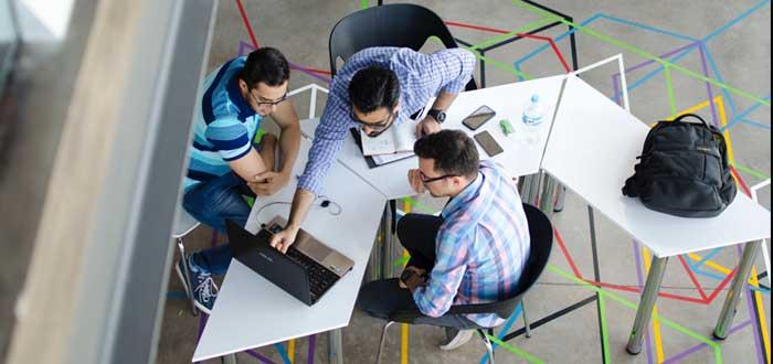 Equipo de hombres trabajan sobre una mesa con un laptop