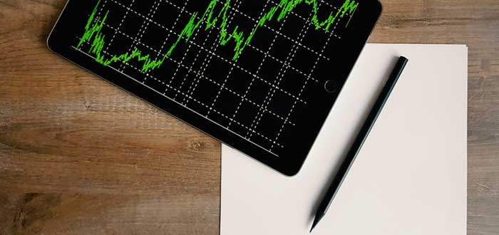 Tablet con gráfico de curva una libreta y un bolígrafo