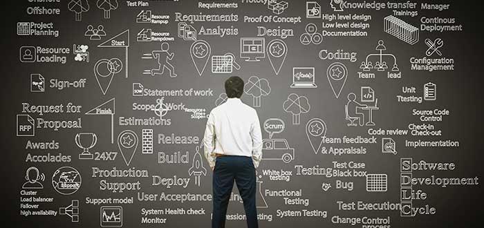 Hombre_mira_tablero_con_procesos_de_empresa para hacer innovación tecnológica