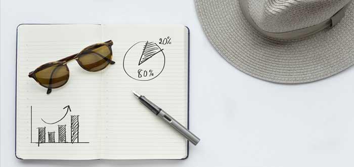 Una agenda con el diagrama Pareto gafas un bolígrafo y un sombrero