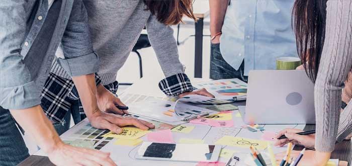 Cuatro personas alrededor de una mesa de trabajo diseñan imagen corporativa