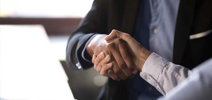 Dos ejecutivos estrechan la mano por las estrategias de crecimiento