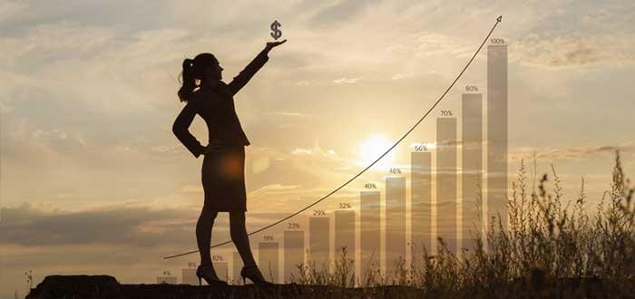 Empresaria con signo de dinero en la mano con atardecer de fondo