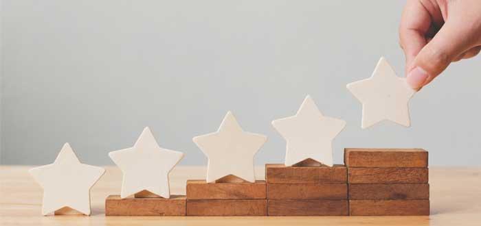 Una escalera hecha con piezas de madera con estrellas encima y una mano de hombre