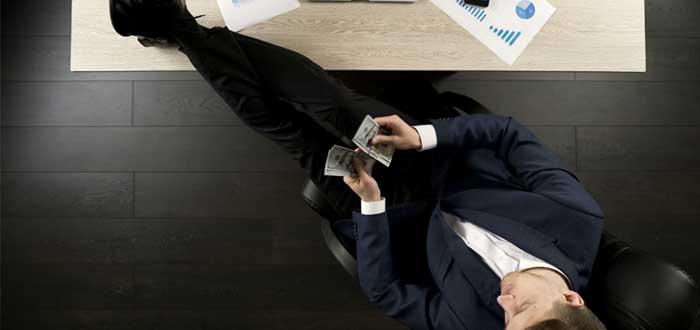 Hombre cuenta dinero con los pies sobre el escritorio y un laptop