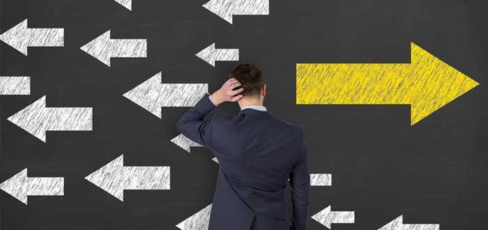 Hombre frente a una pared negra con flechas blancas hacia la izquierda y flecha amarilla hacia la derecha
