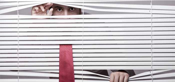 Hombre mira desde una persiana blanca cerrada