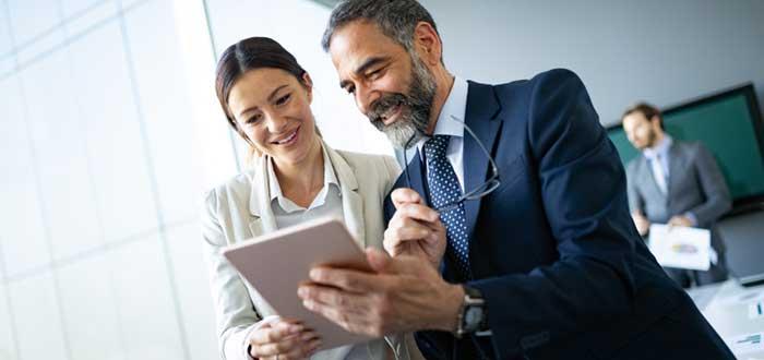 Hombre y mujer miran tablet con imagen corporativa