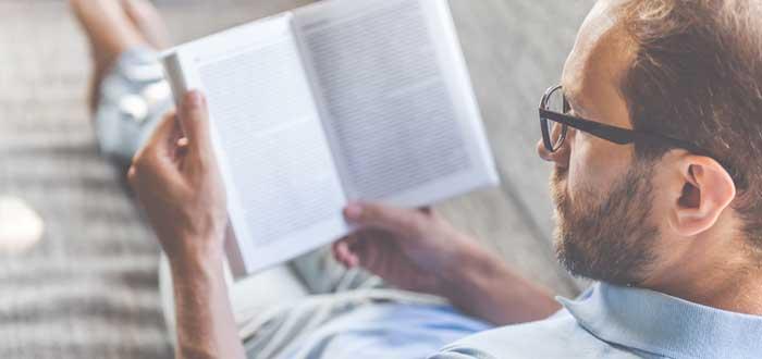 Hombre recostado leyendo un libro abierto