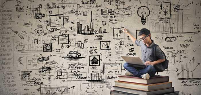Hombre sentado sobre libros con una laptop y haciendo anotaciones en una pared