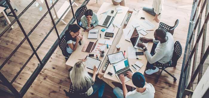 Hombres y mujeres conversan y trabajan en un escritorio con laptop y notas