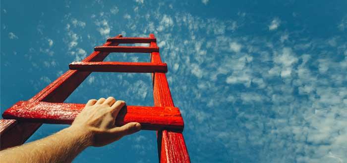 Mano de hombre en una escalera roja que apunta al cielo