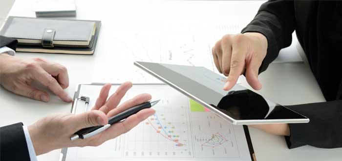 Manos de dos hombres con una tablet sobre la mesa hacen proyecciones de imagen corporativa