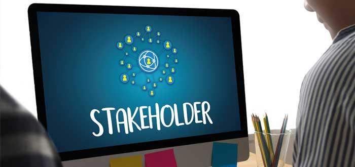 Un monitor con letrero de stakeholders y hombre que analiza las estrategias de crecimiento