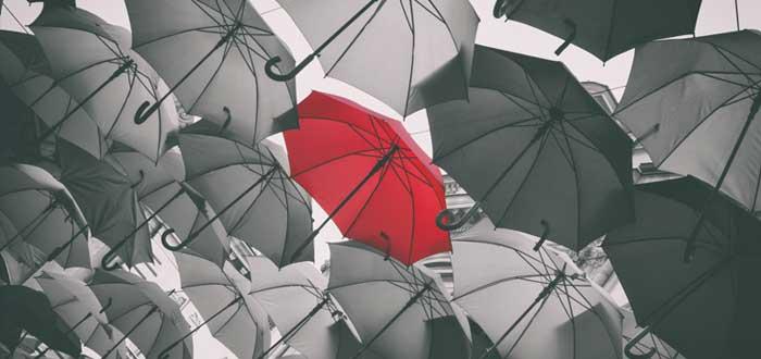 Muchos paraguas negros y un paraguas rojo