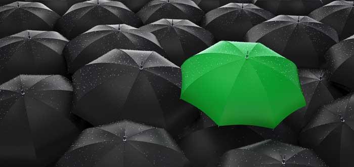 Muchos paraguas negros y uno verde