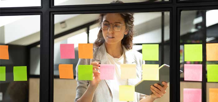 Mujer fija papeles de colores en una ventana
