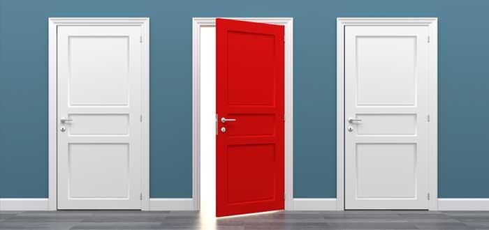 Puerta roja abierta entre puertas blancas cerradas