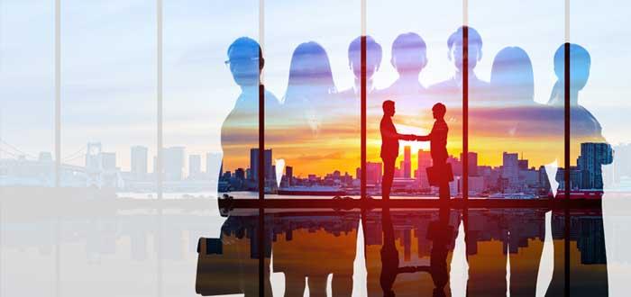 Siluetas de empresarios estrechando la mano con una ciudad al fondo
