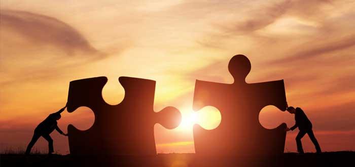 Silueta de hombres que empujan fichas gigantes de puzzle