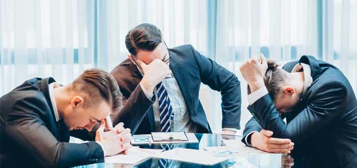 Tres ejecutivos sentados alrededor de una mesa se lamentan