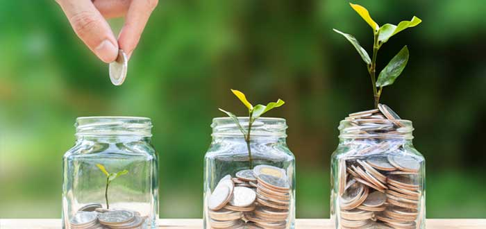 Frascos con monedas y plantas sembradas como símbolo de inversión