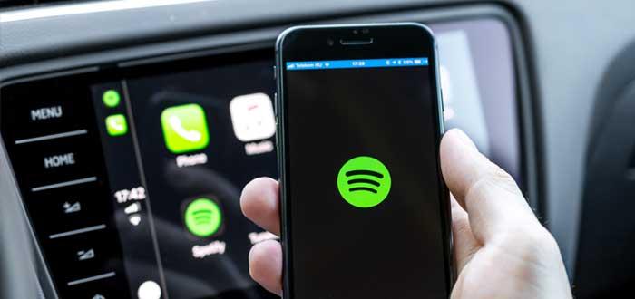 Hombre en un auto sostiene teléfono celular con logotipo de Spotify