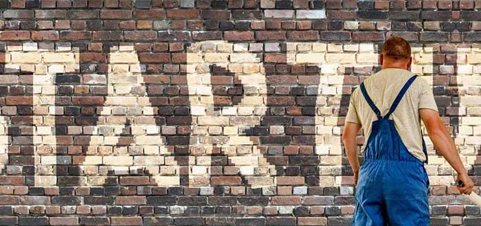 Un hombre pinta un muro con el letrero startup